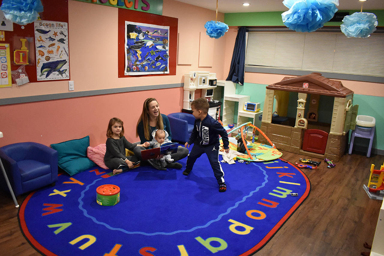 Daycare owner Nicholle Dhaliwal sits with her son Midas while two of the kids in her charge, Charli Krahn (4) and Amari Crawford (3), play around her.                                Grace Kennedy photo
